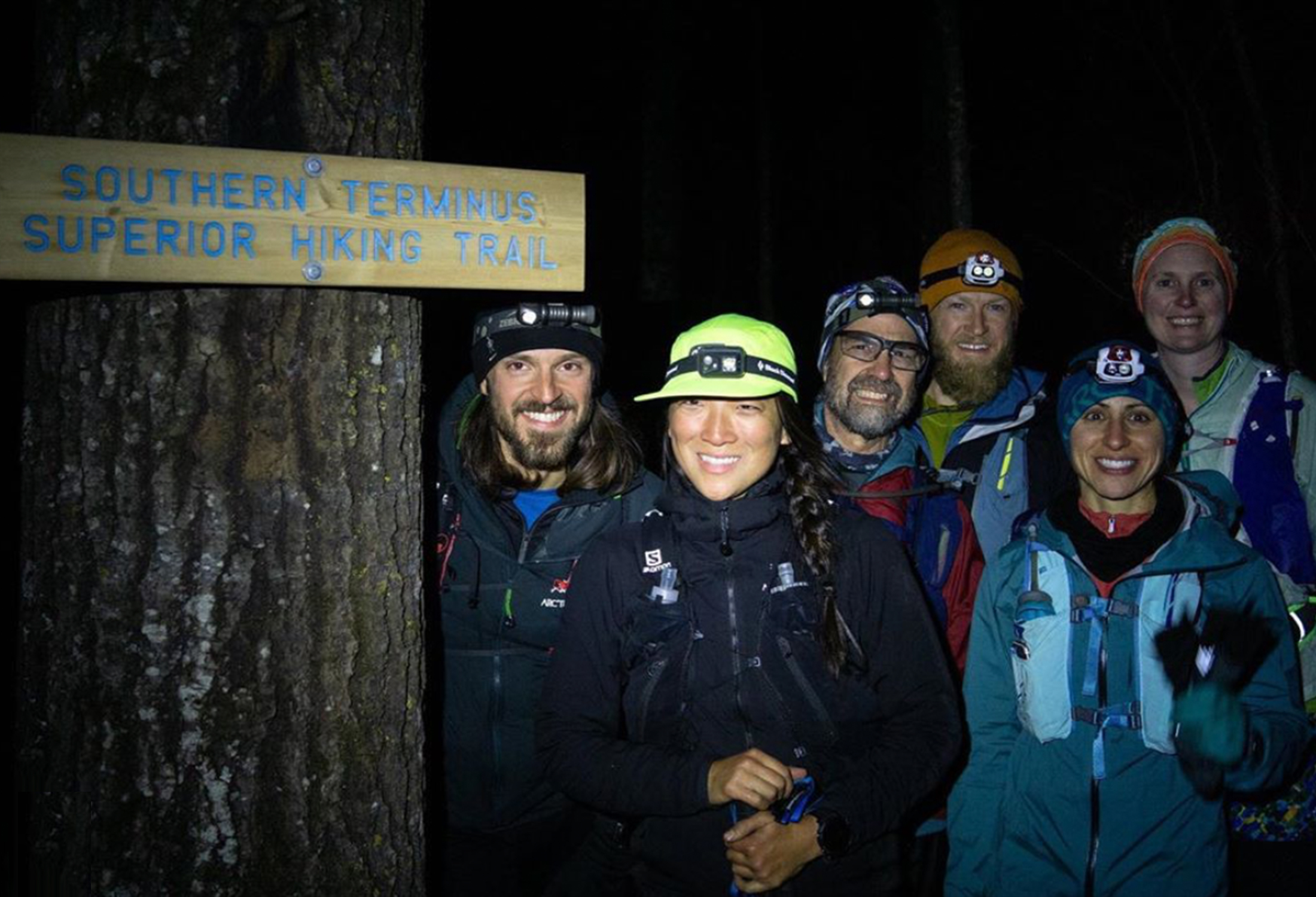 Alex Elizabeth and crew smiling at night next to southern terminus trail sign