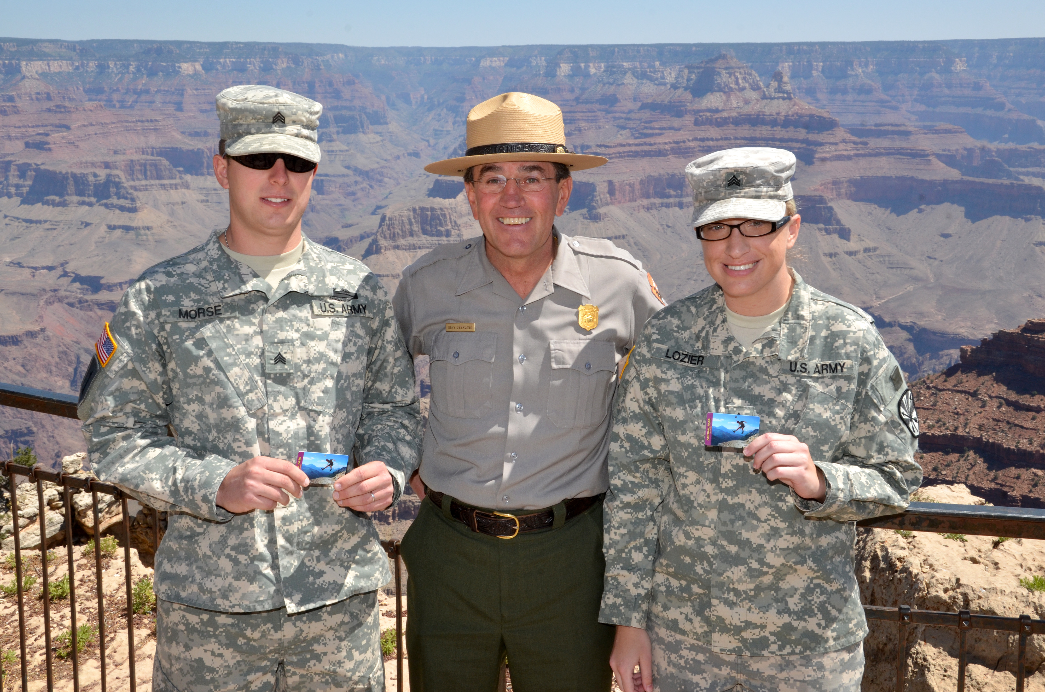 two military members and one ranger smiling at camera and holding up park passes at Grand Canyon National Park