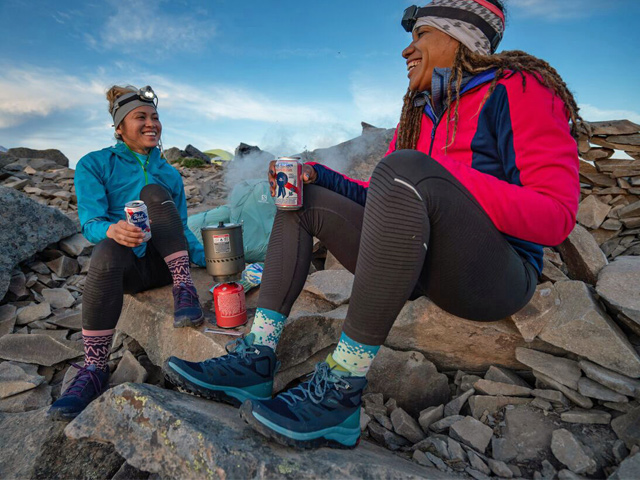 Two Black women wearing Salomon shoes and jackets, headlamps, and holding beers sitting in boulderfield
