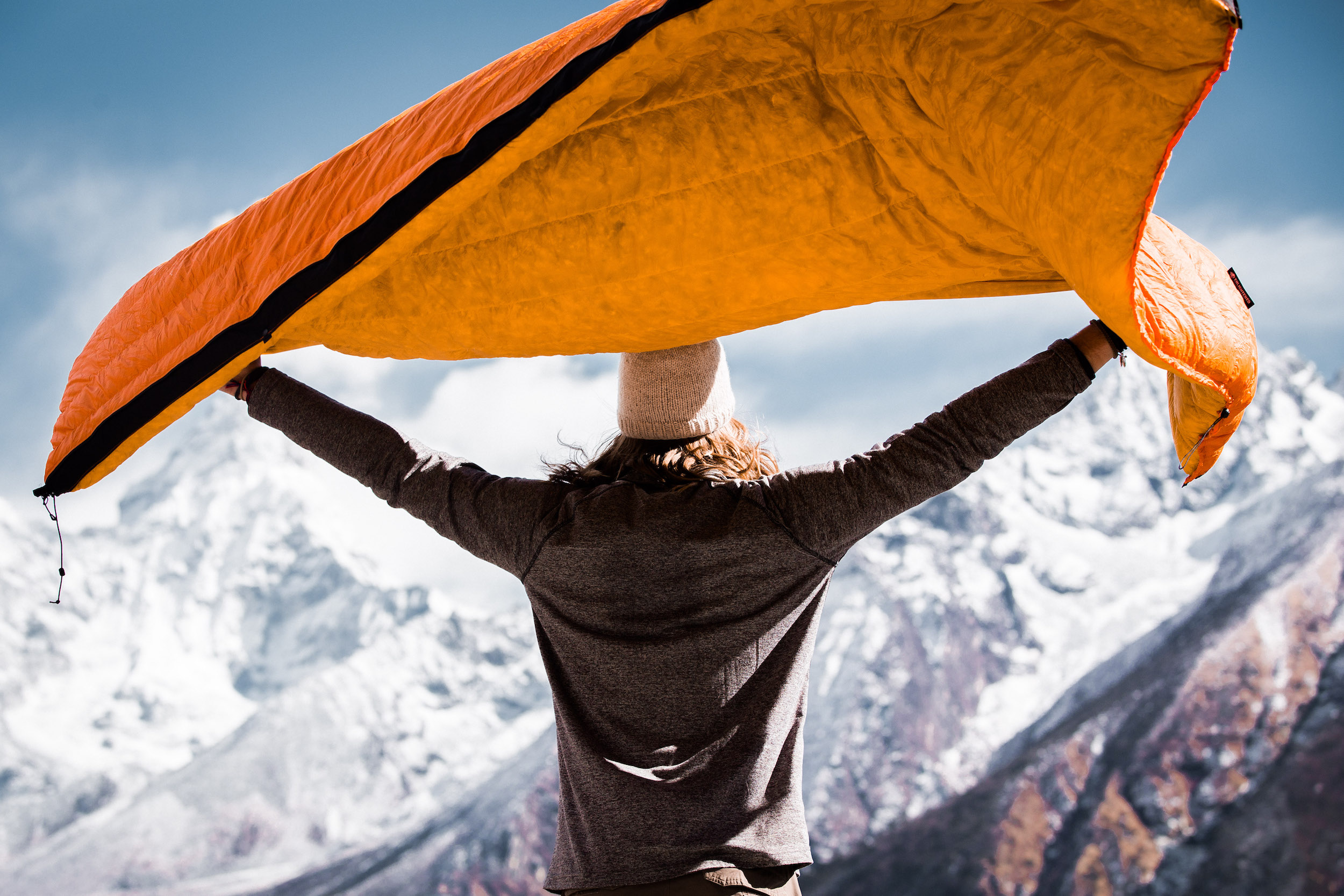 person with arms outstretched holding up Enlightened Equipment quilt in the wind in the mountains