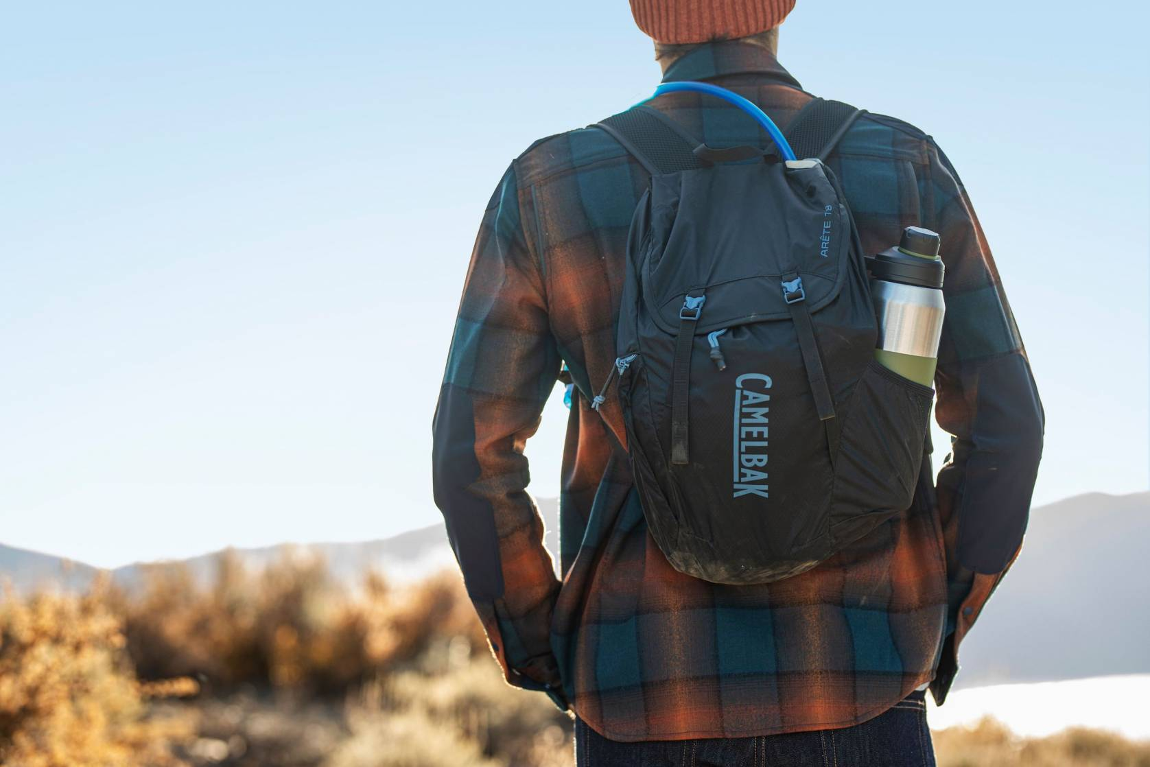 Person in burnt orange beanie and flannel facing away from camera wearing a Camelbak Pack