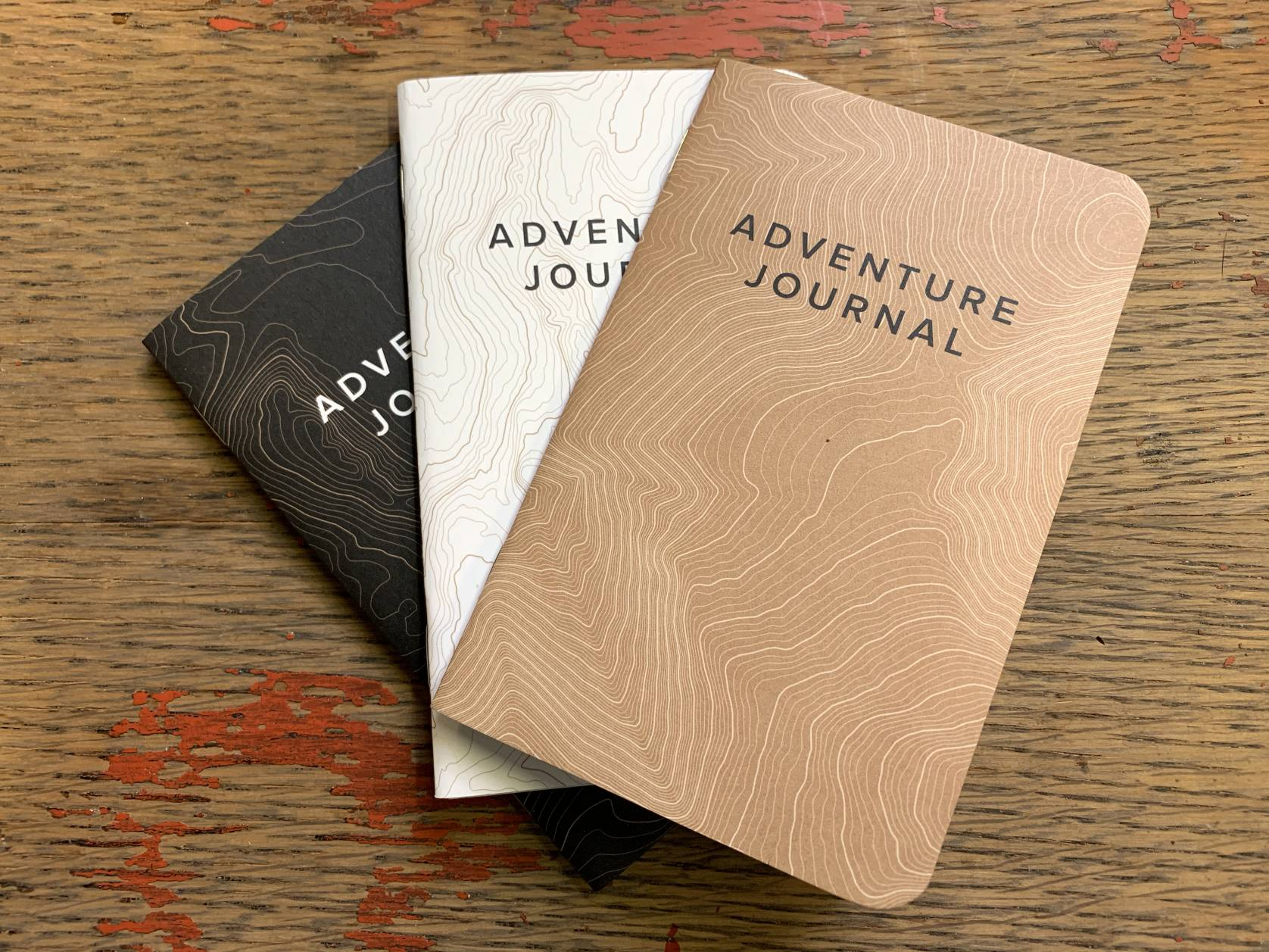 trio of adventure journal notebooks fanned out on table