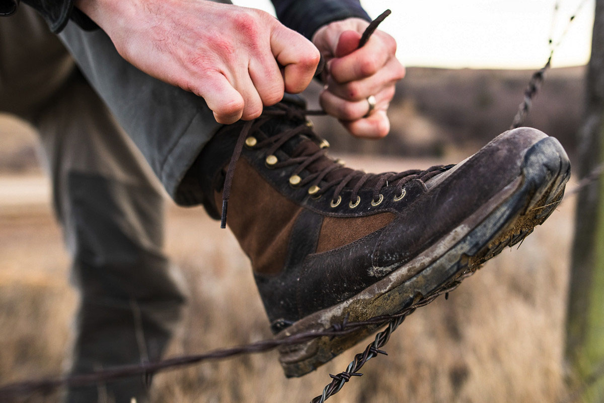 Man resting foot on wire fence to tie shoe on Danner recurve boot