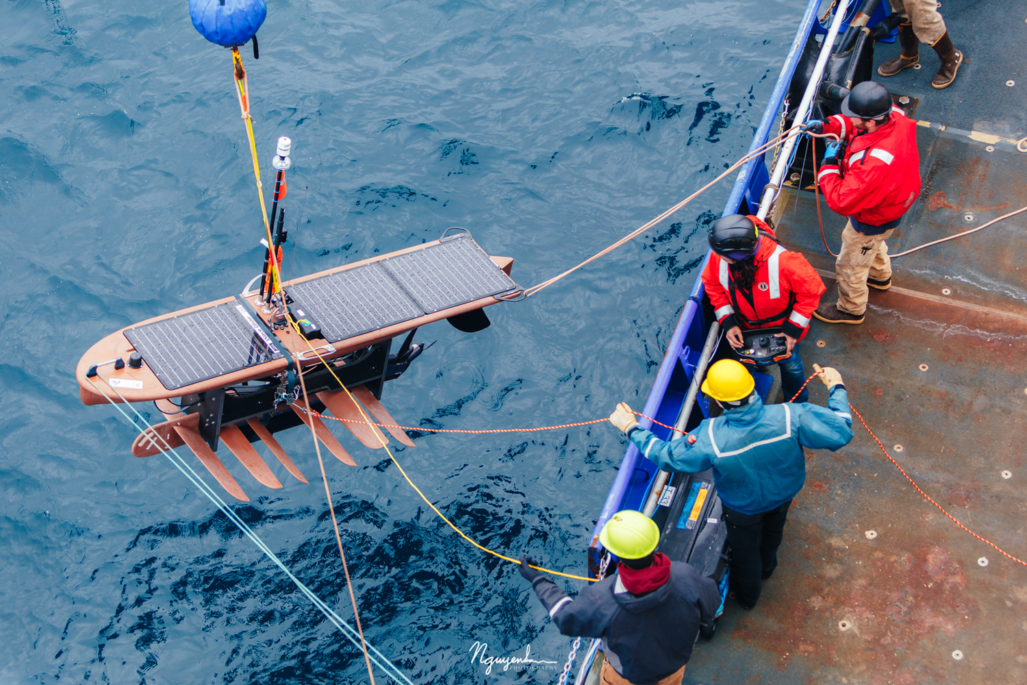 workers on barge lowering The Wave Glider surfboard down in the ocean