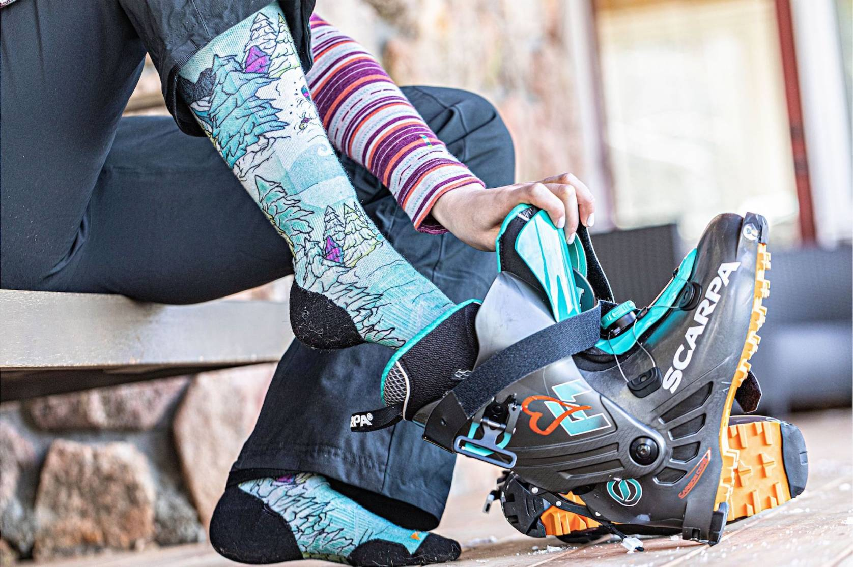 skier putting on Smartwool socks and ski boots