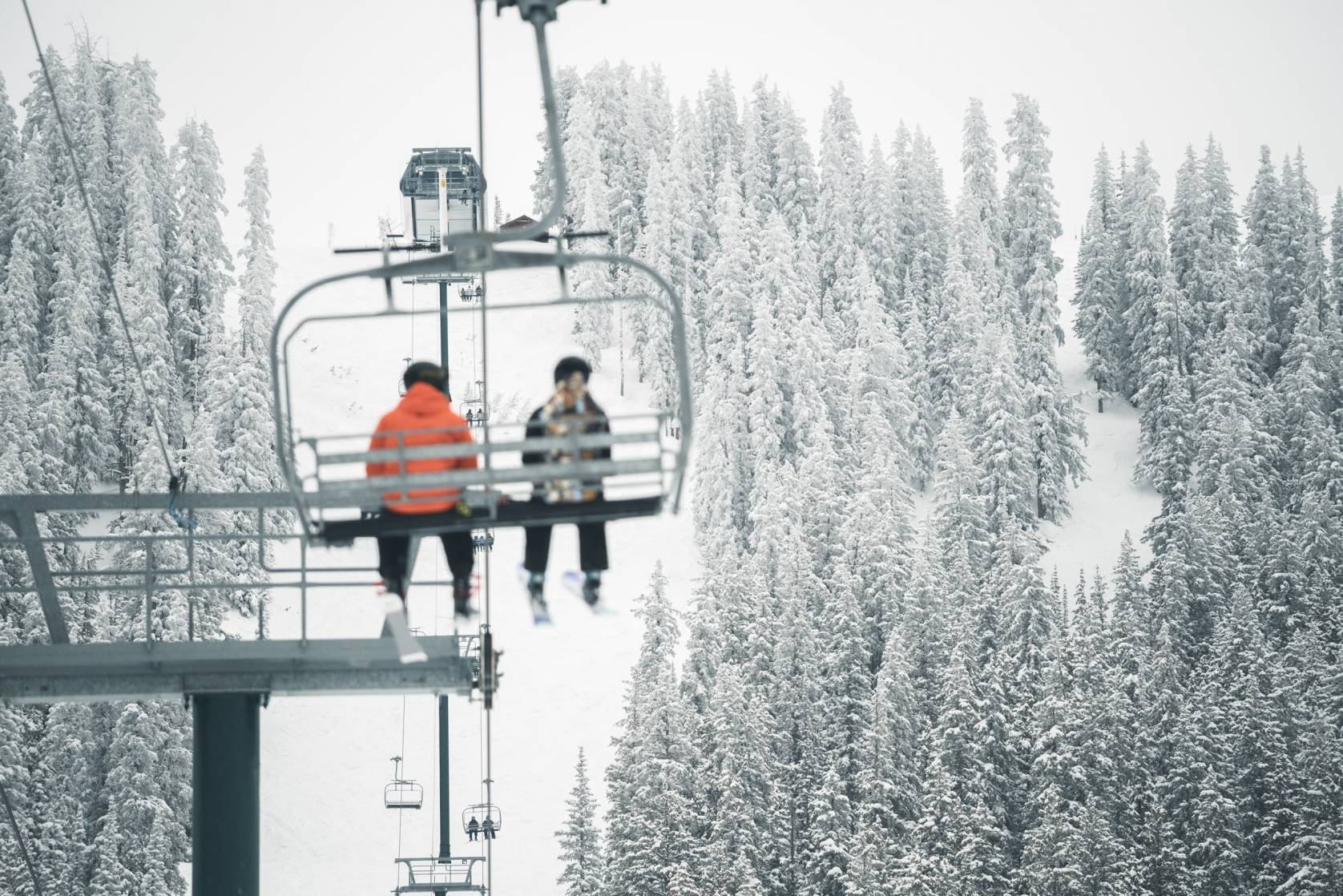 Backcountry Semiannual Sale Skiers in Mountains on Chairlift with Snowy Trees