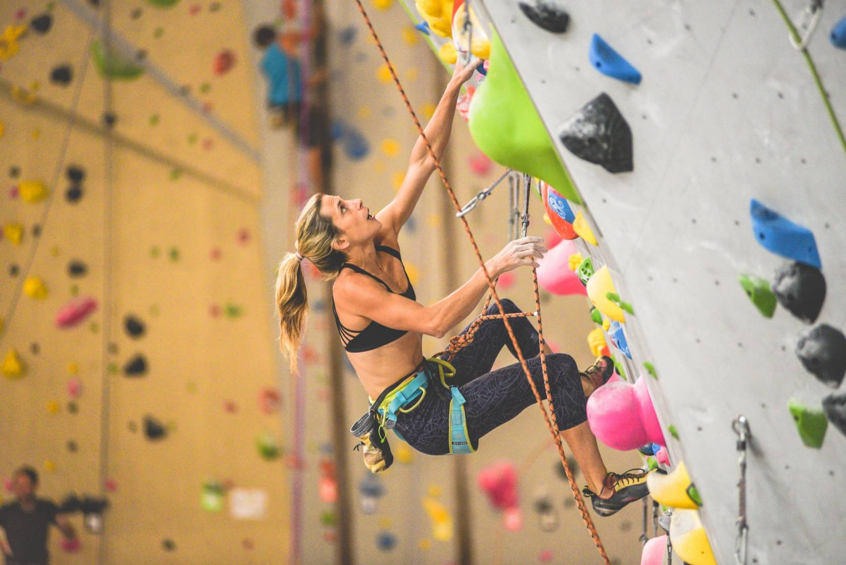 woman in sports bra and tights lead climbing at Movement Climbing + Fitness gym