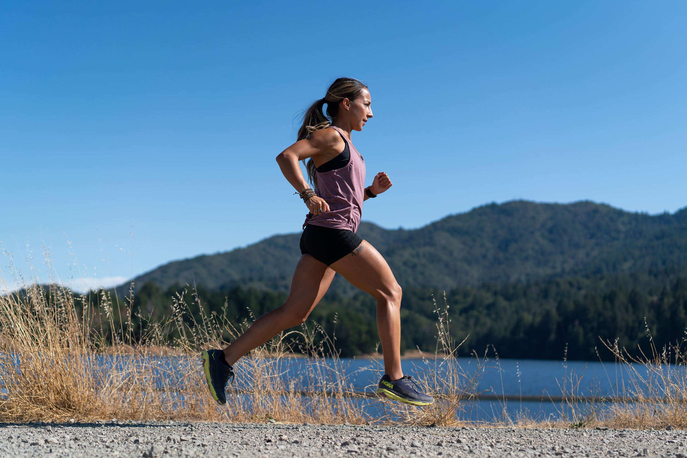 Woman trail running in Hoka One One shoes on sunny day