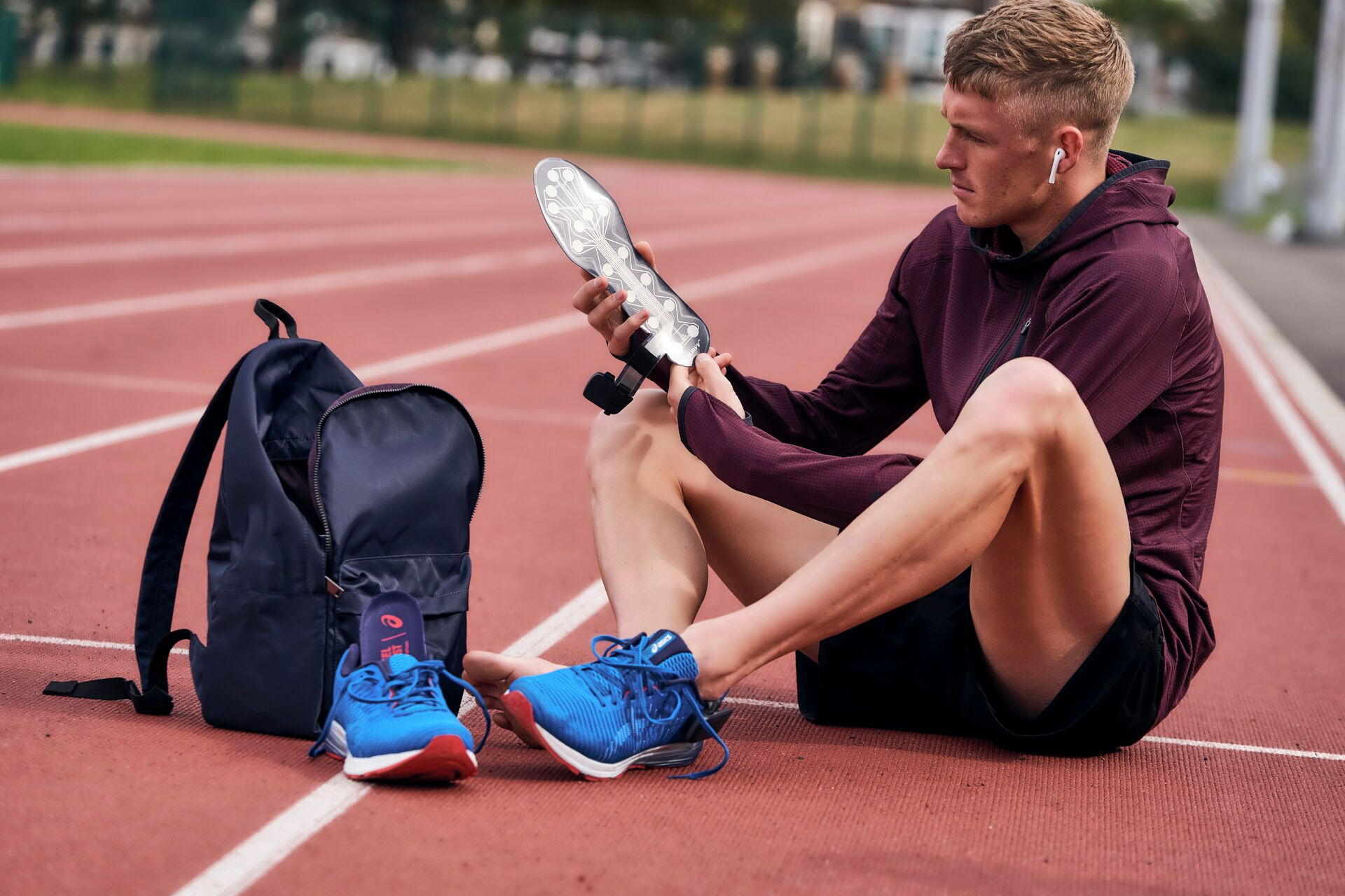 Man sitting on track wearing earbuds and putting on NURVV Run biometric and app-connective Insoles
