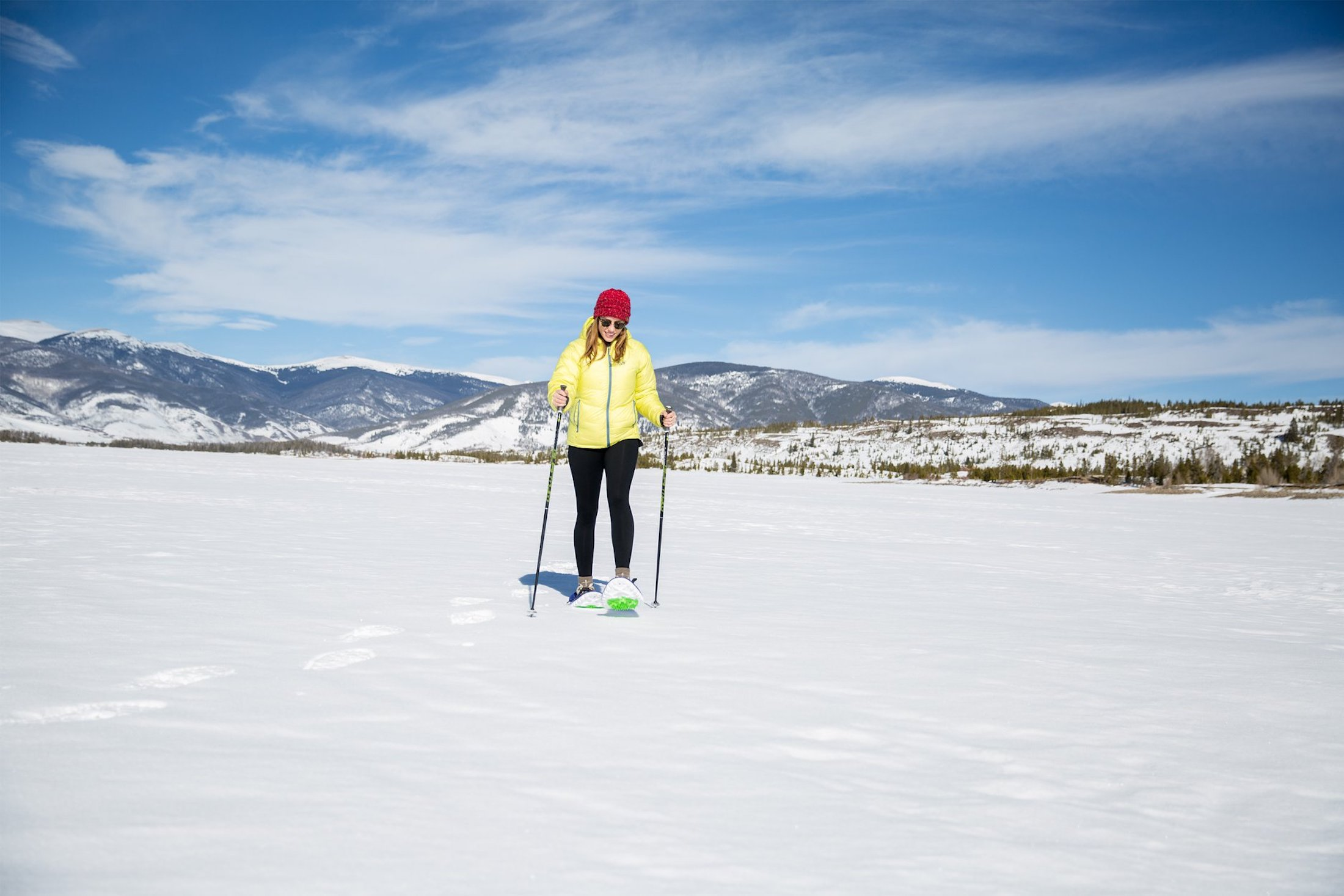 woman in red beanie snowshoeing with crescent moon across flat snow
