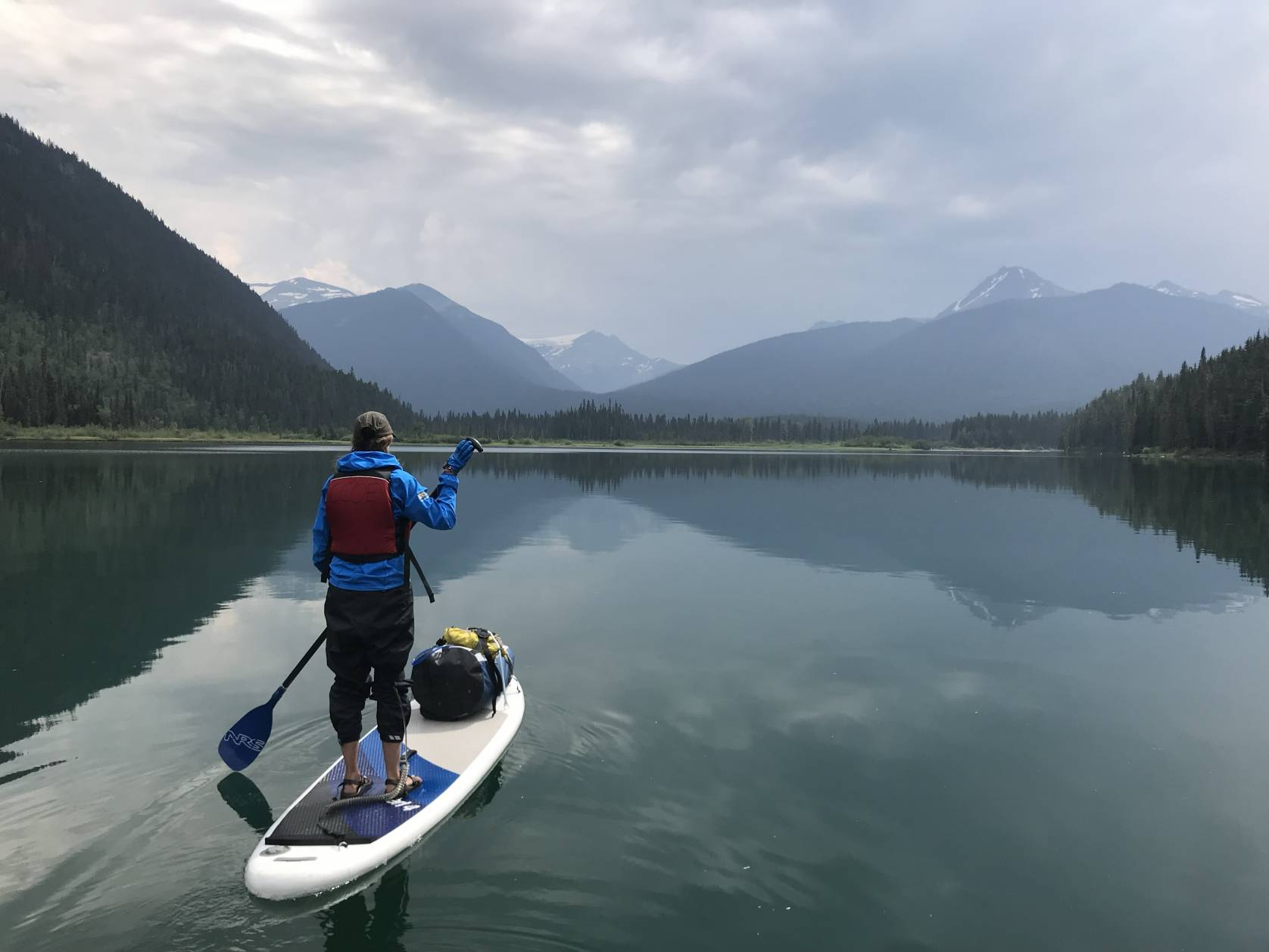 Author Mary in long sleeves and red PFD paddle boarding across flat water lake in British Columbia