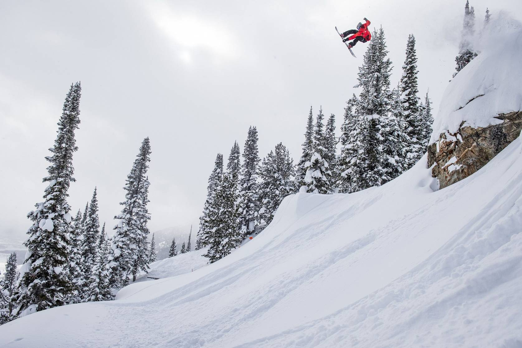 snowboarder in red jacket flying off jump in right of photo at Natural Selection Tour practice session