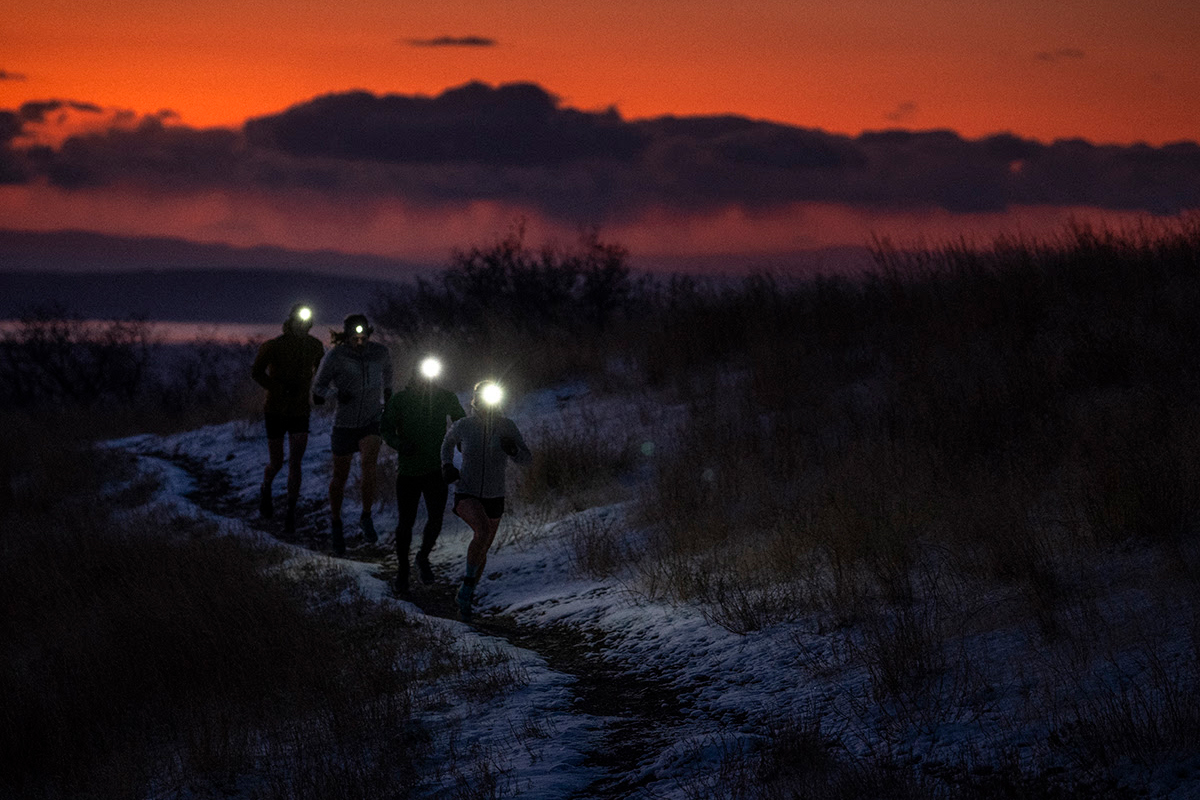 Trail Runners Wearing Black Diamond Headlamps with orange sunset in background