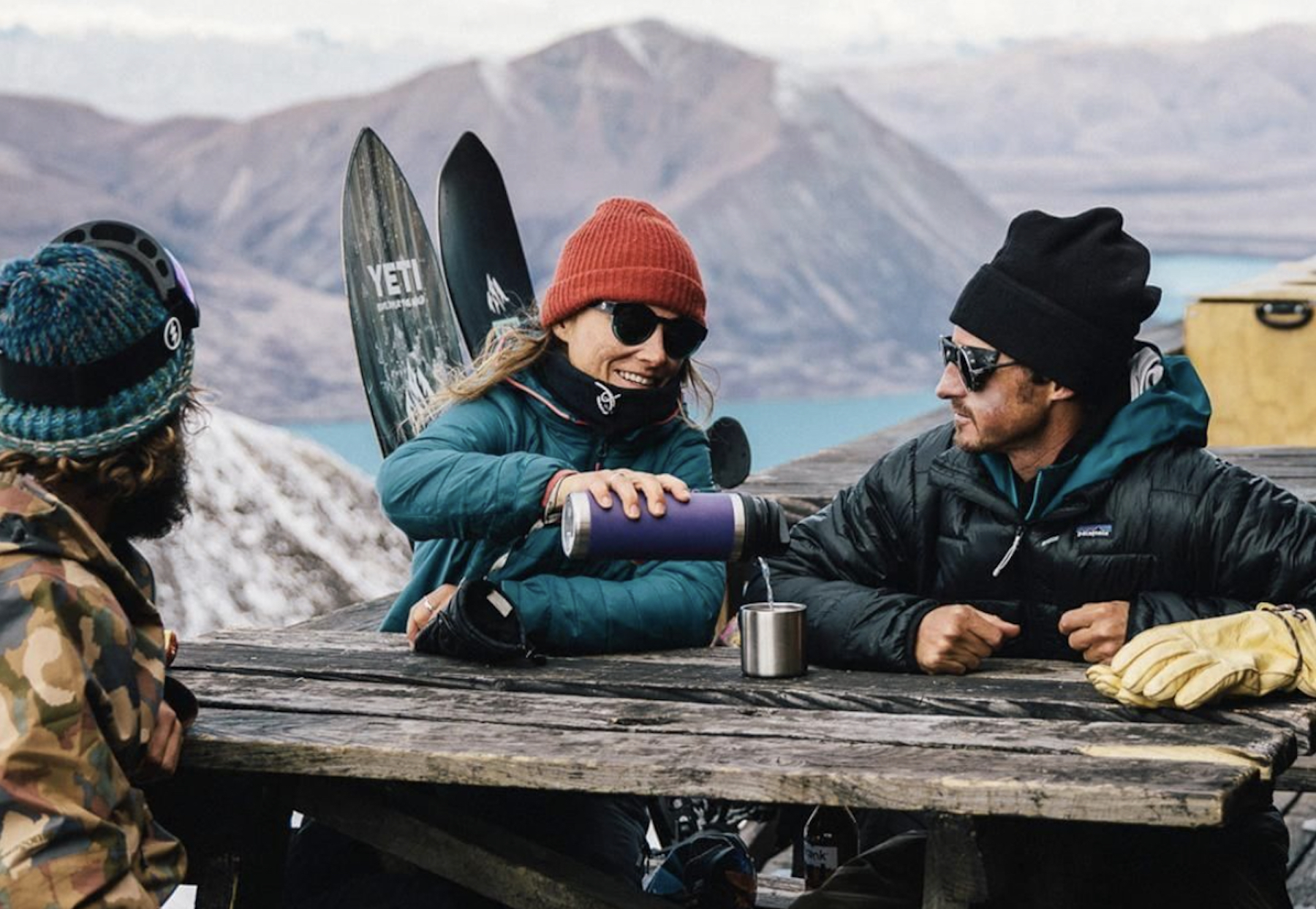 3 skiers in sunglasses looking over mountains, one pouring drink from purple YETI bottle