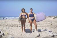 Danielle Lyons and another female surfer carrying surfboards