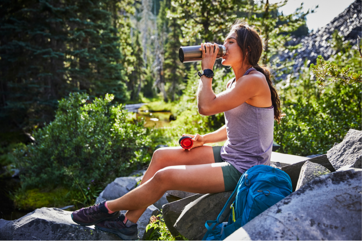 A woman drinking from a 32 ounce Hydro Flask Trail Series bottle