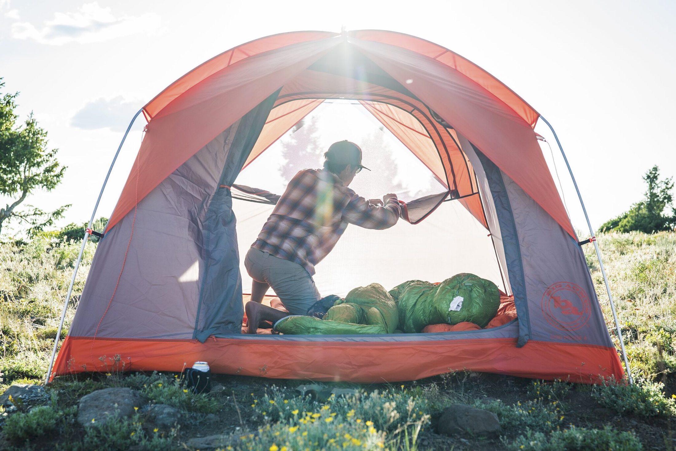 man zipping open door in 4-person Big Agnes tent