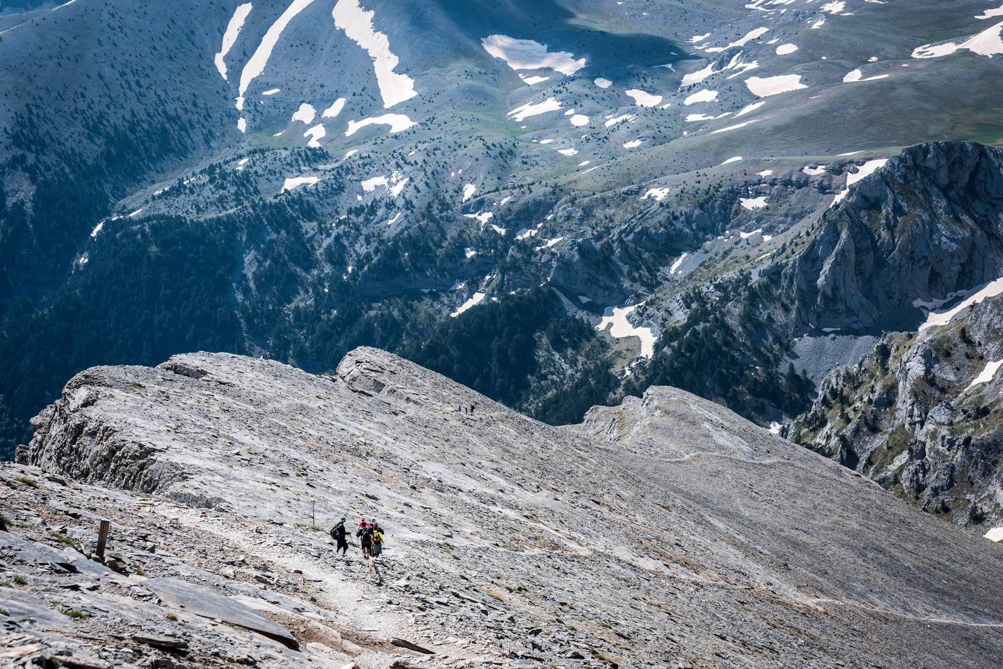 small people in distance trekking across rocks in Greece