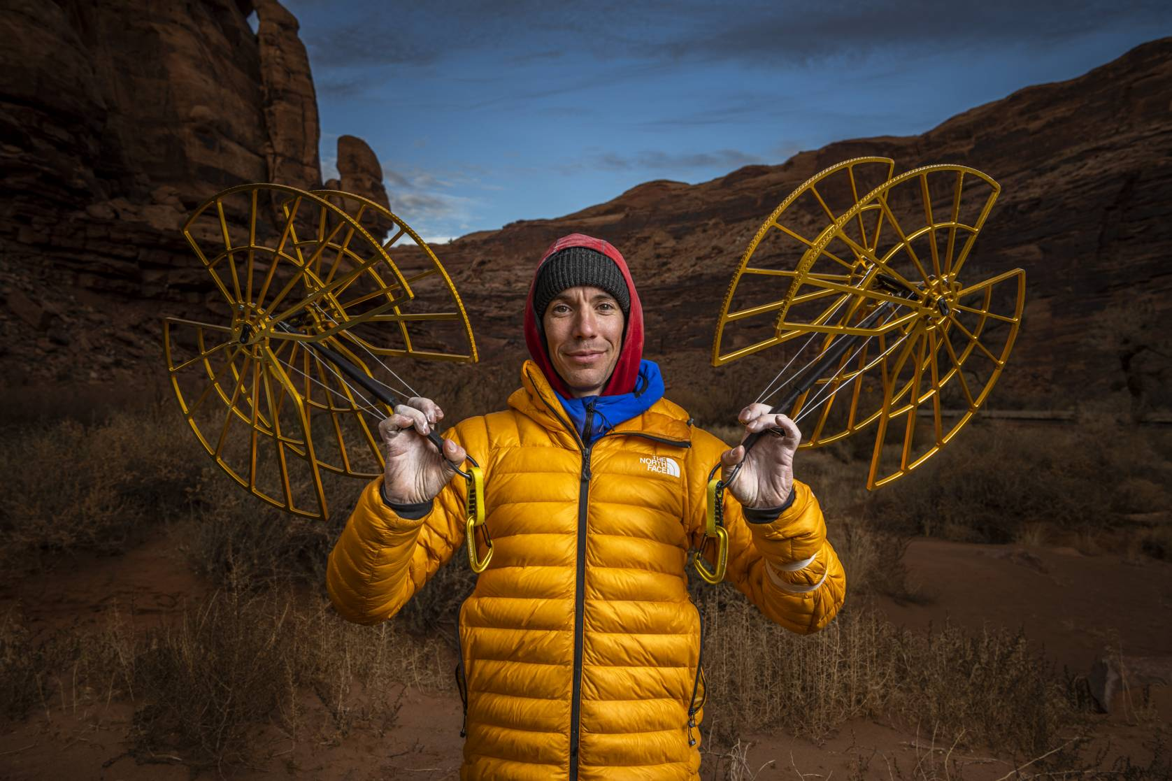 Alex Honnold in a yellow puffy and beanie holding giant 2-foot cams