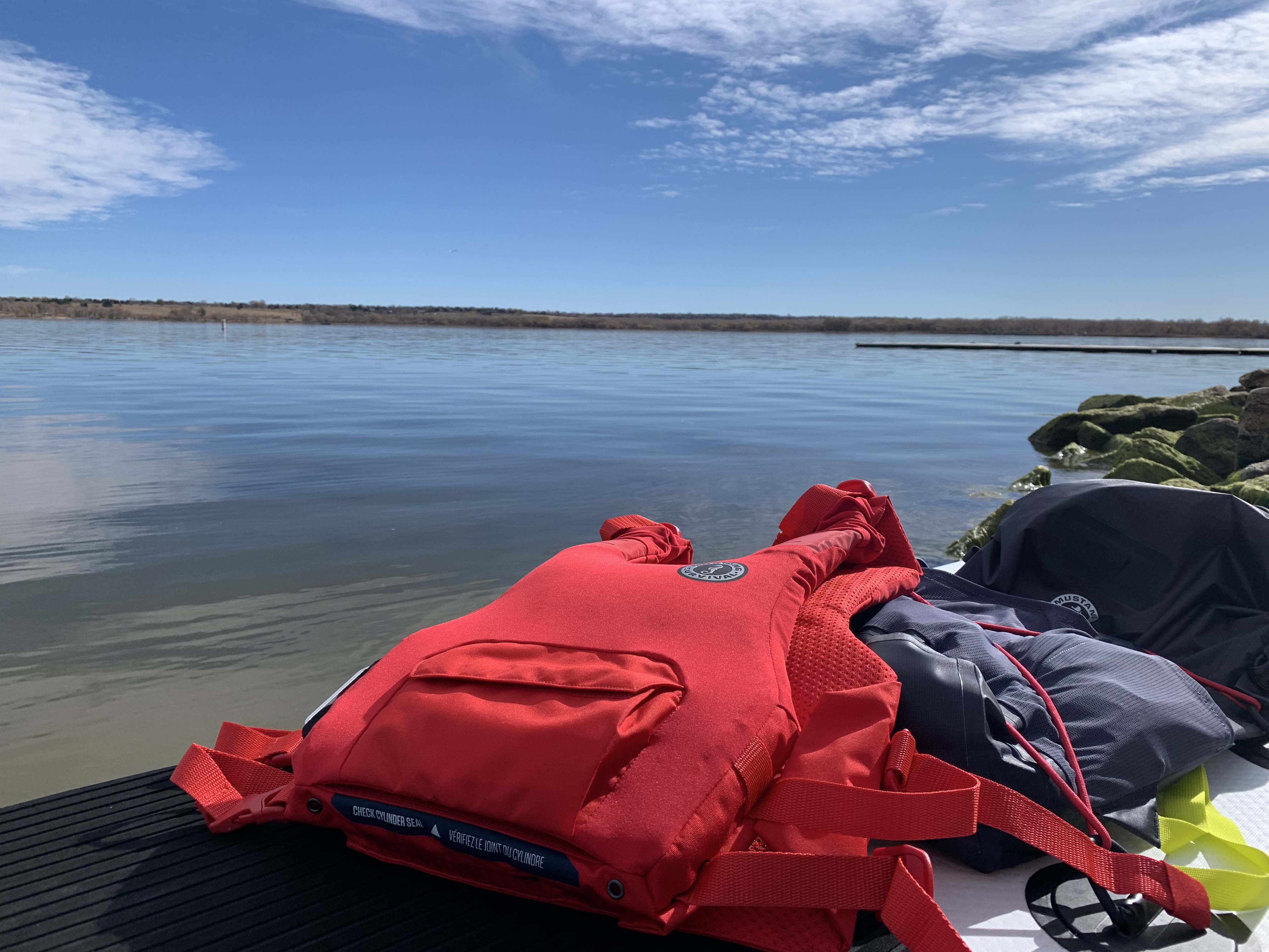 Mustang Survival Khimera PFD resting next to dry bag on deck of paddleboard near a still lake