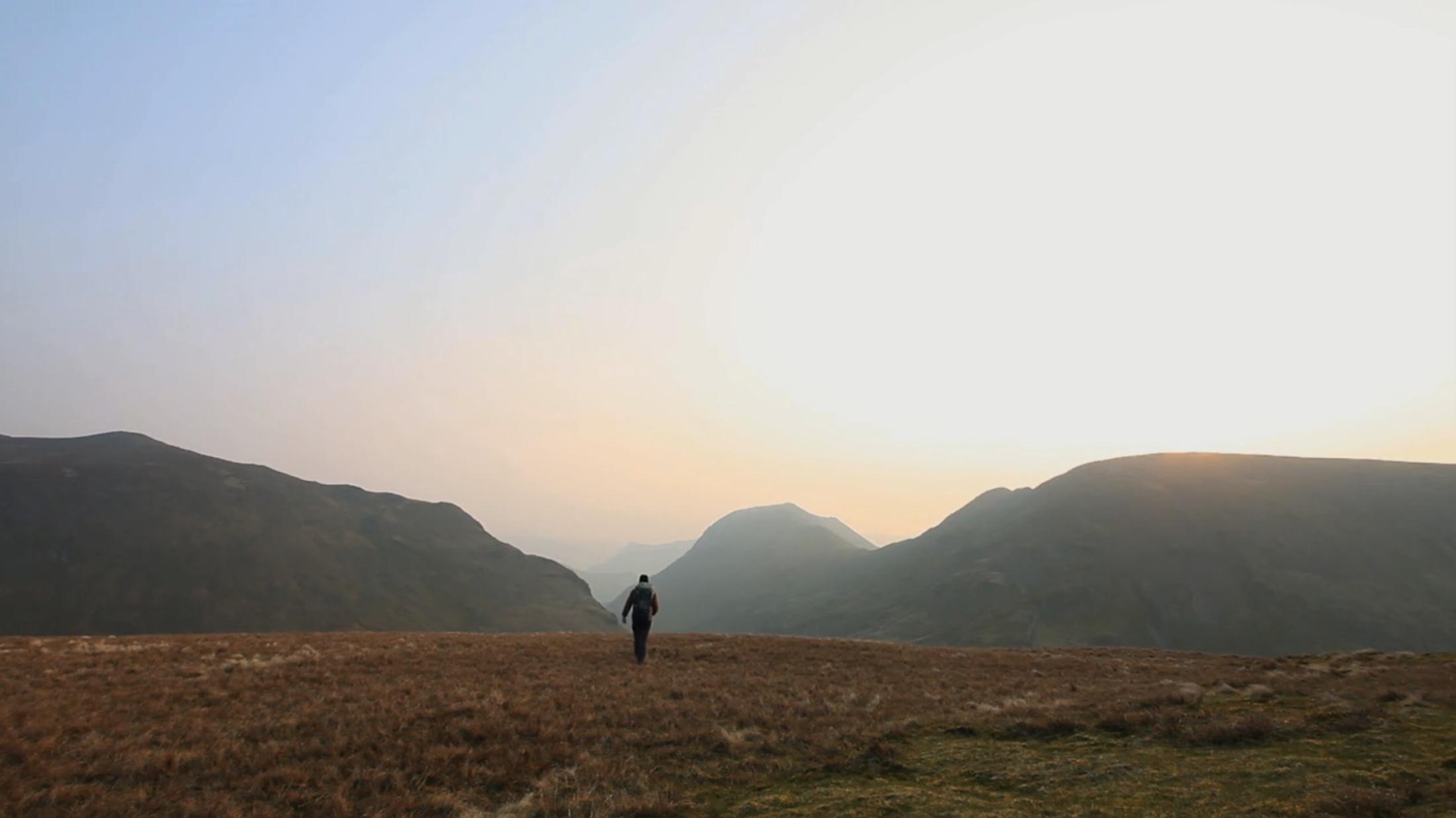alastair humphreys hiking towards edge of field at dusk