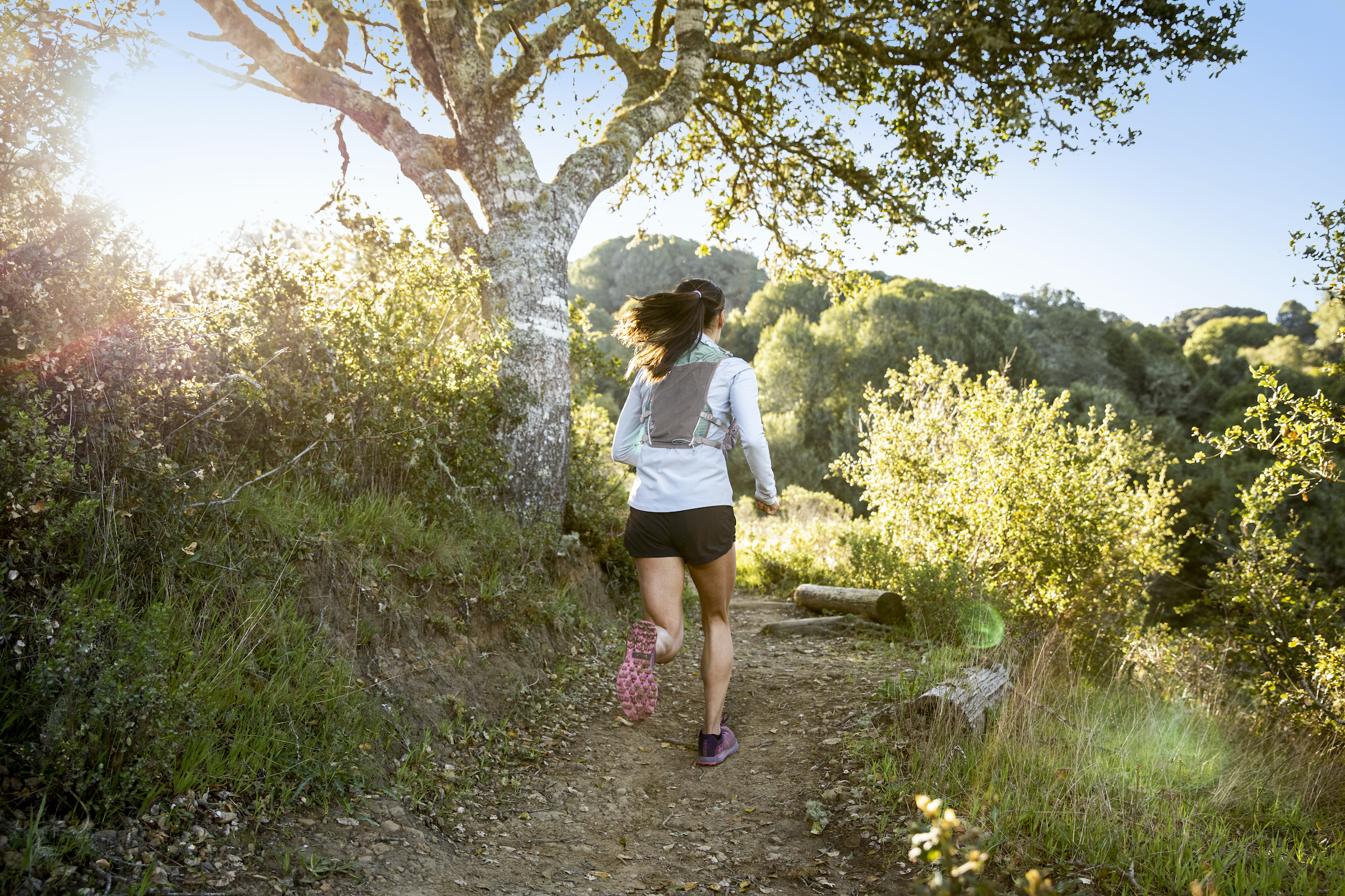 woman with black ponytail running in Camelbak Zephyr Vest and long sleeve