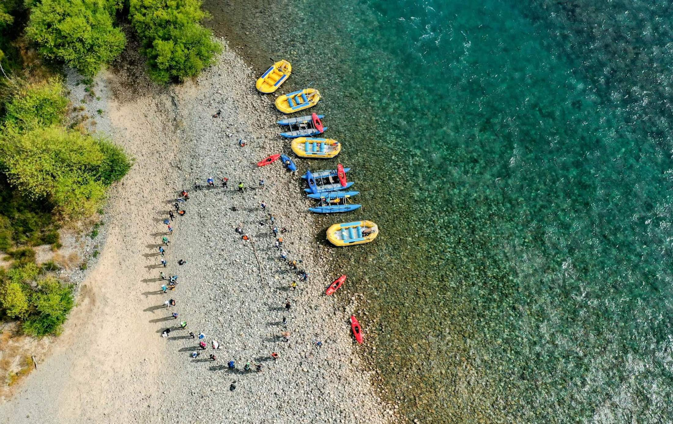 birds eye view of First Descents paddlers and rafts on rocky shore