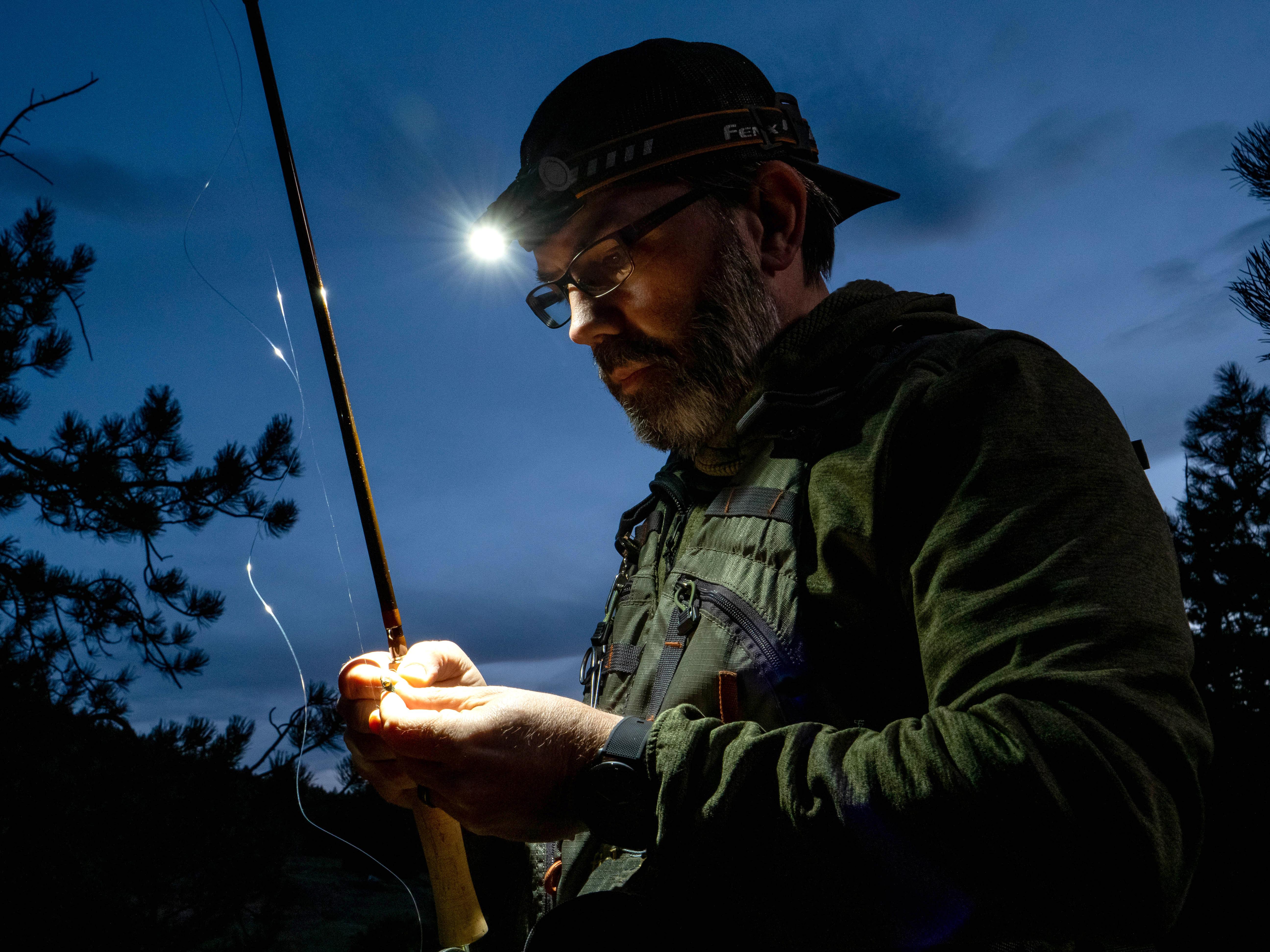 Man Tying Fly Wearing Fenix Headlamp Fly Fishing