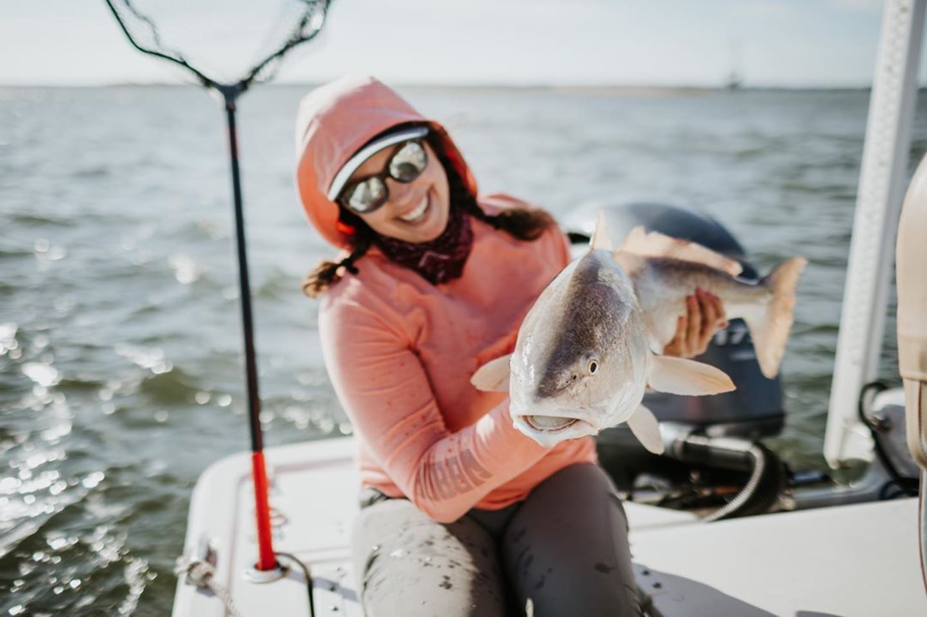 Woman holding fish on boat