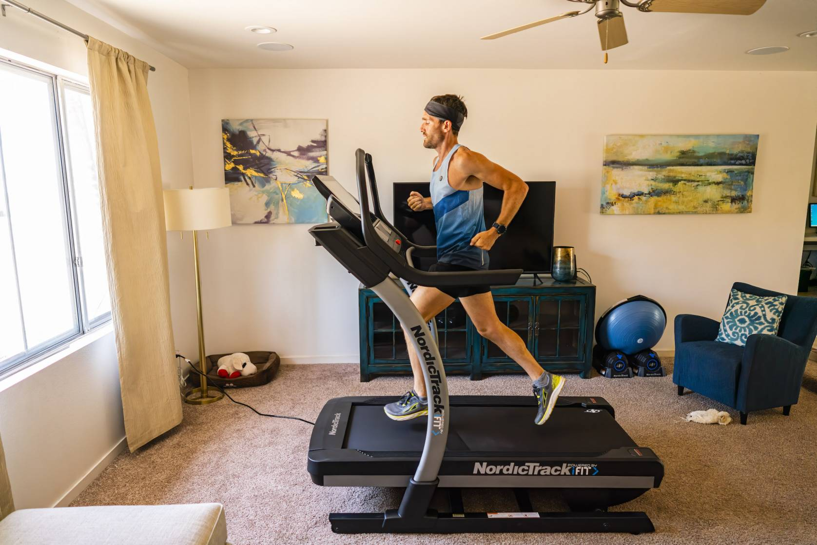 Zach Bitter in headband and tank running 100 miles on treadmill