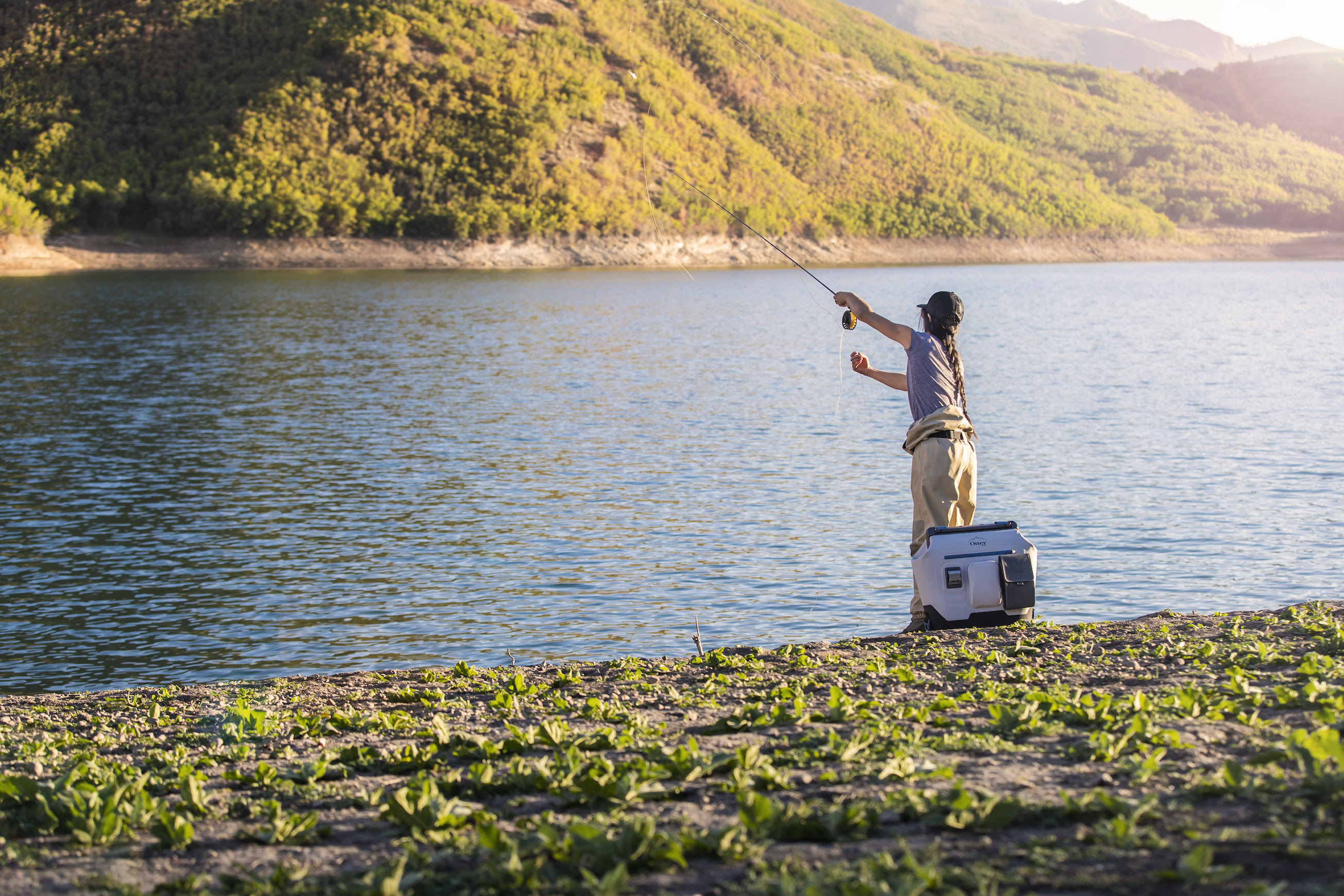 female angler on shore of lake with OtterBox trooper cooler