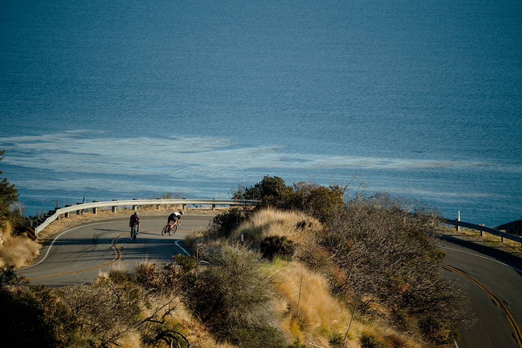 People road cycling with ocean