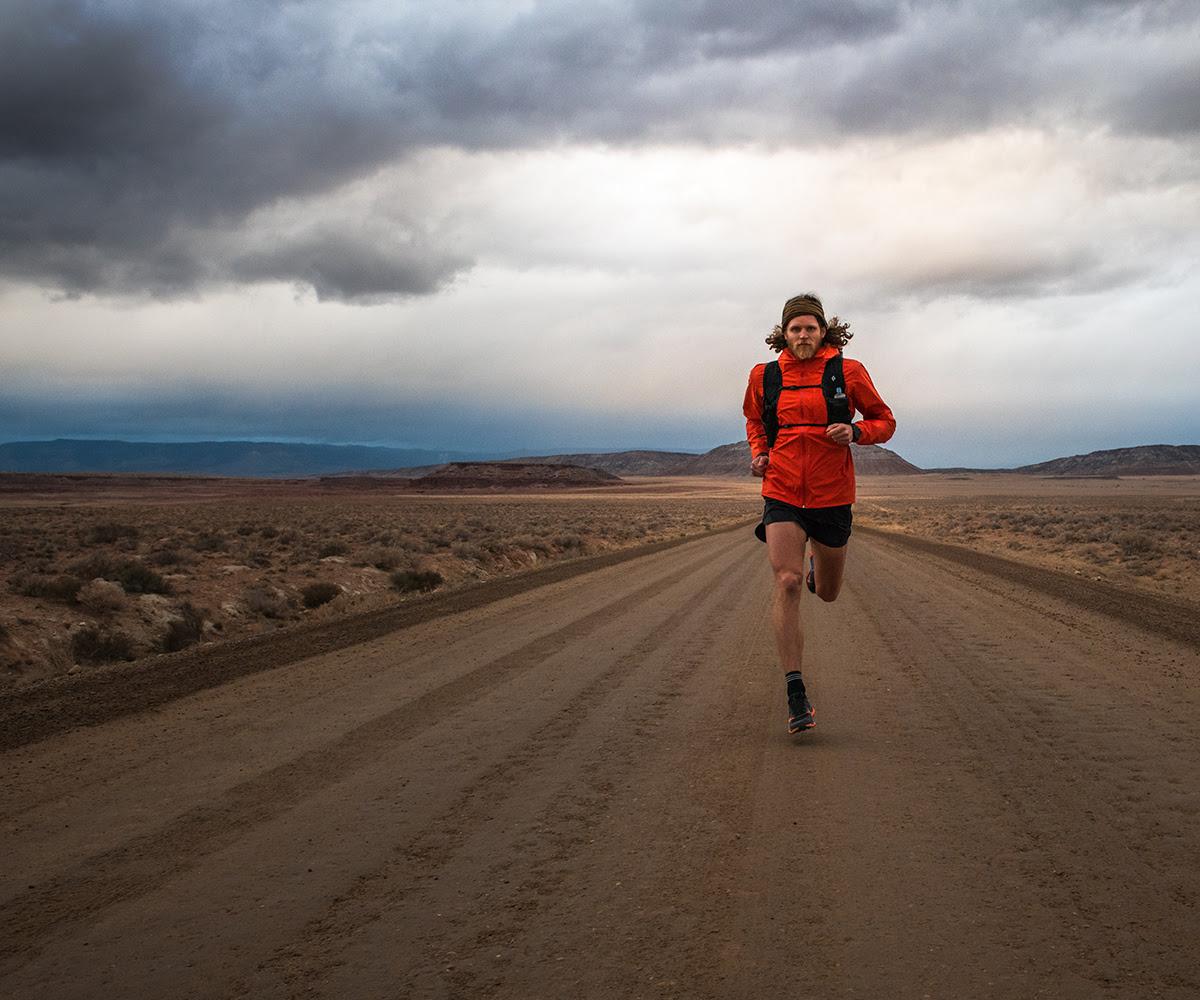 Man Running on a gravel road in Black Diamond gear