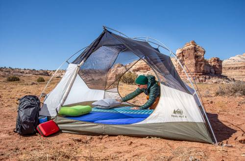person in puffy jacket setting up REI tent in southwest landscape
