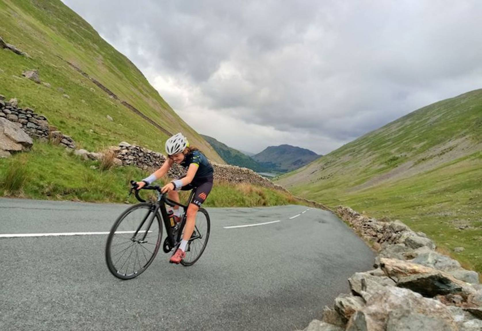 cyclist hannah rhodes-patterson riding hard up paved mountain road