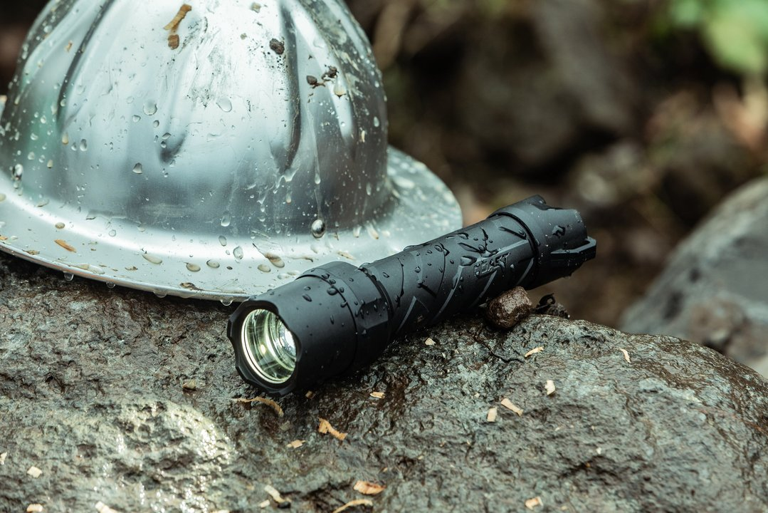 polysteel 600 flashlight resting on wet rock next to hardhat