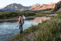Person Fishing in a Simms Fly Fishing Hoody Simms Waders and boots