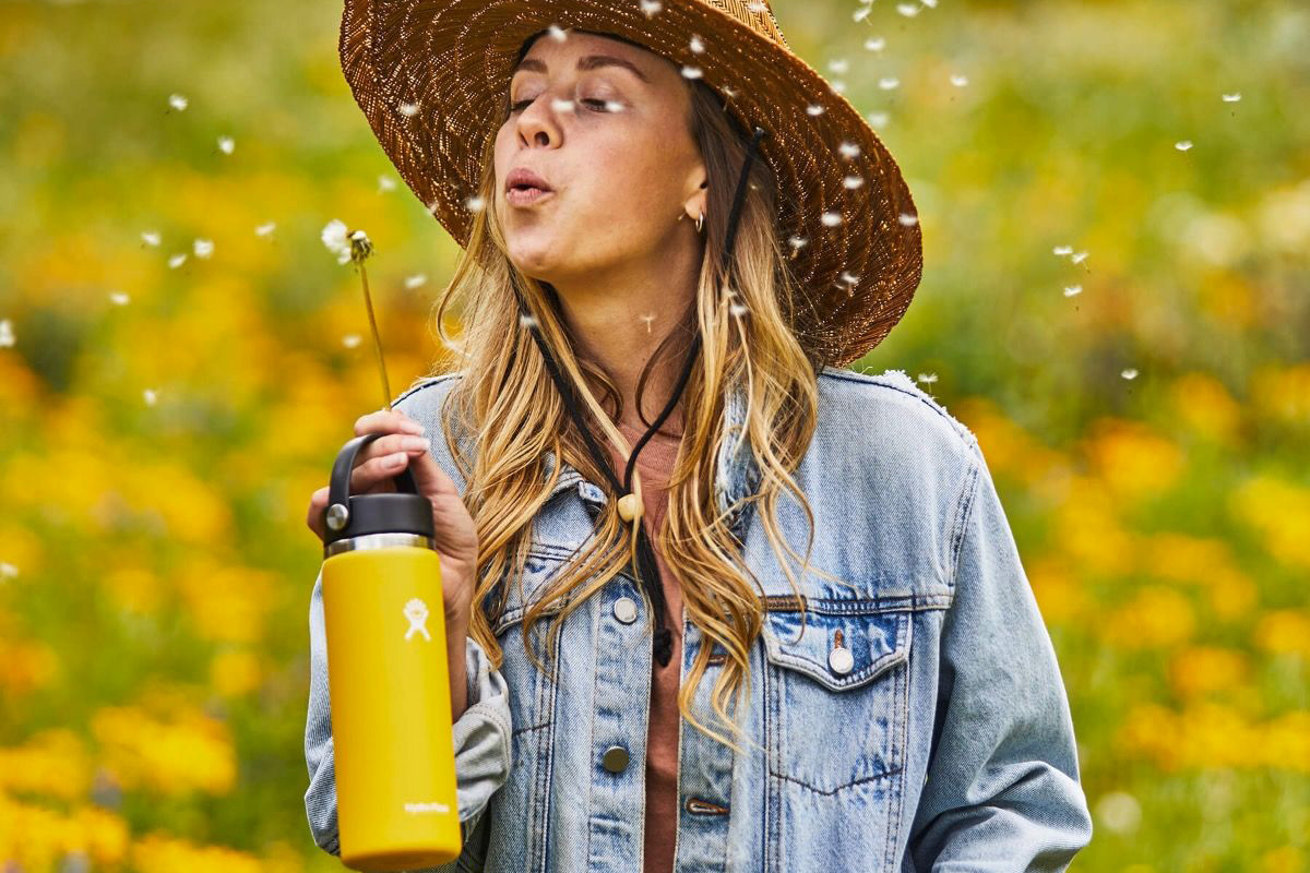 Holding-a-yellow-Hydro-Flask-water-bottle-blowing-a-dandelion