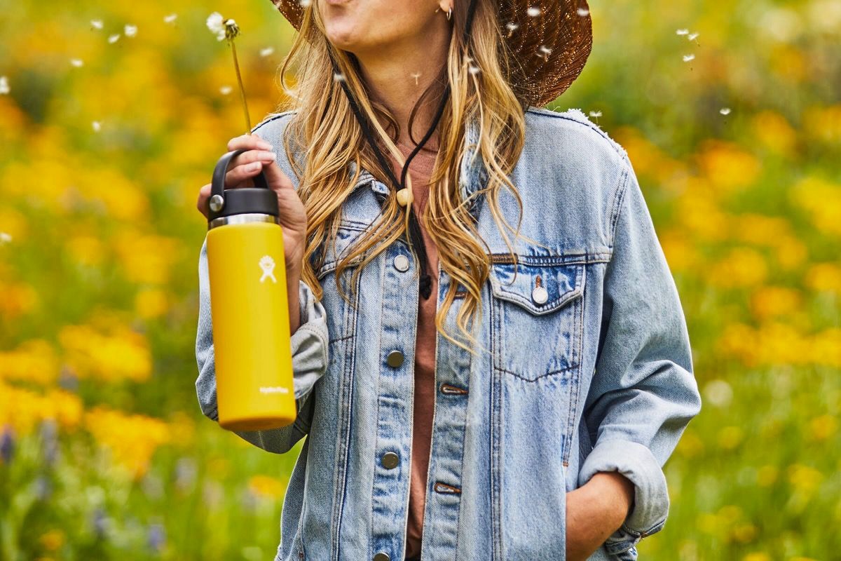Holding-a-yellow-Hydro-Flask-water-bottle-blowing-a-dandelion1