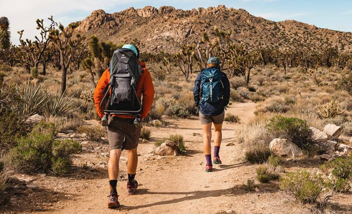 People hiking in the desert with backpacks