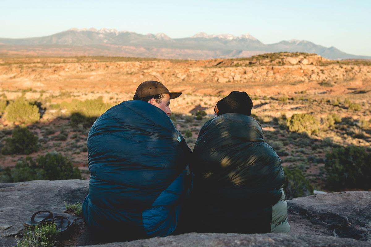People sitting in sleeping bags enjoying the scenery