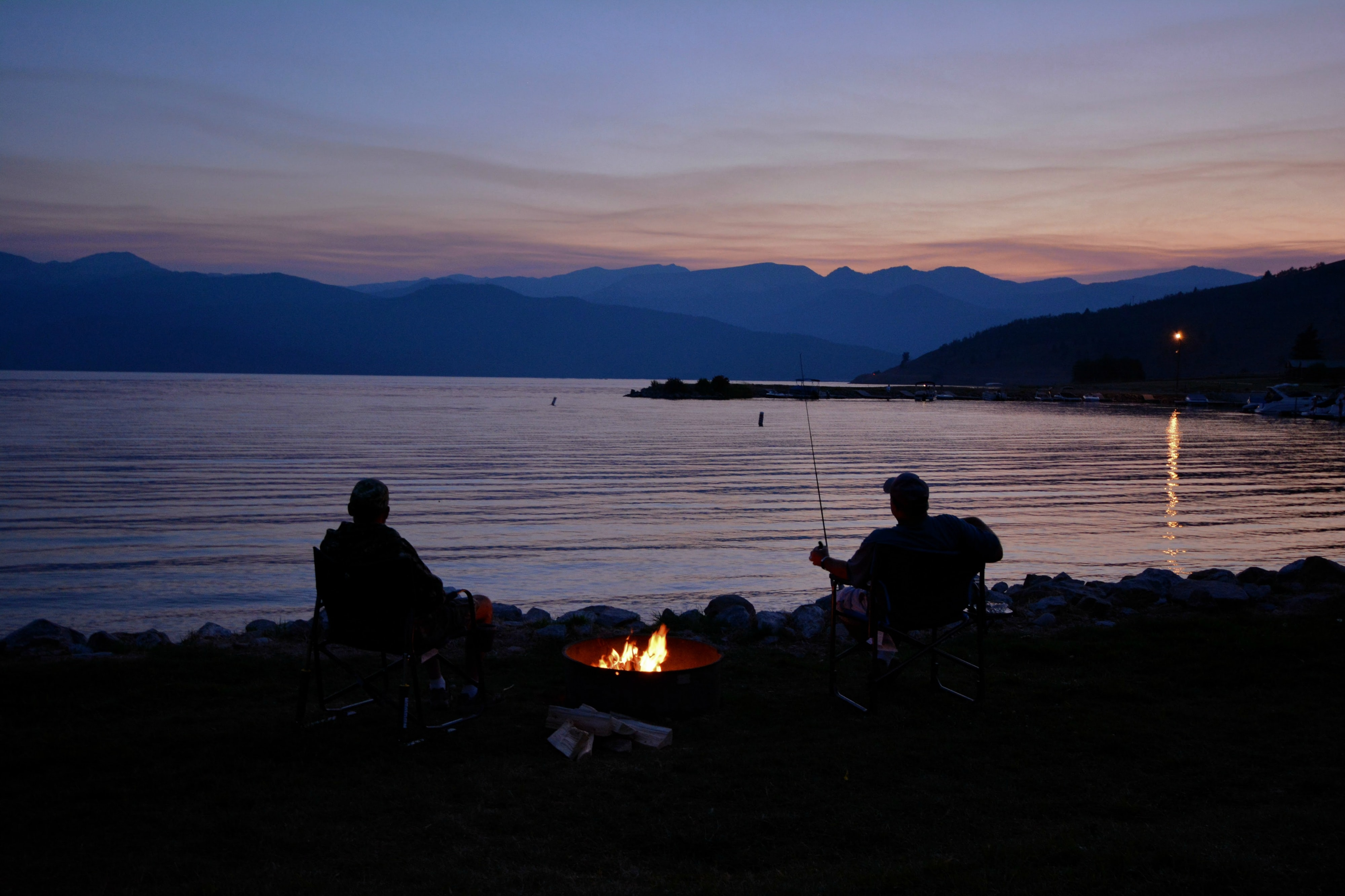 Two people sitting by campfire and lake