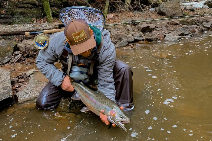 Fly Fisherman Holding Steelhead Fish In River