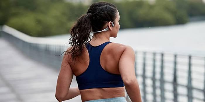 woman running in sports bra along boardwalk wearing AfterShokz headphones
