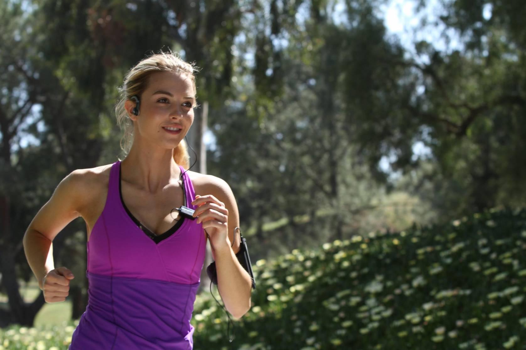 woman in magenta tank top running with AfterShokz Bone Conduction Headphones