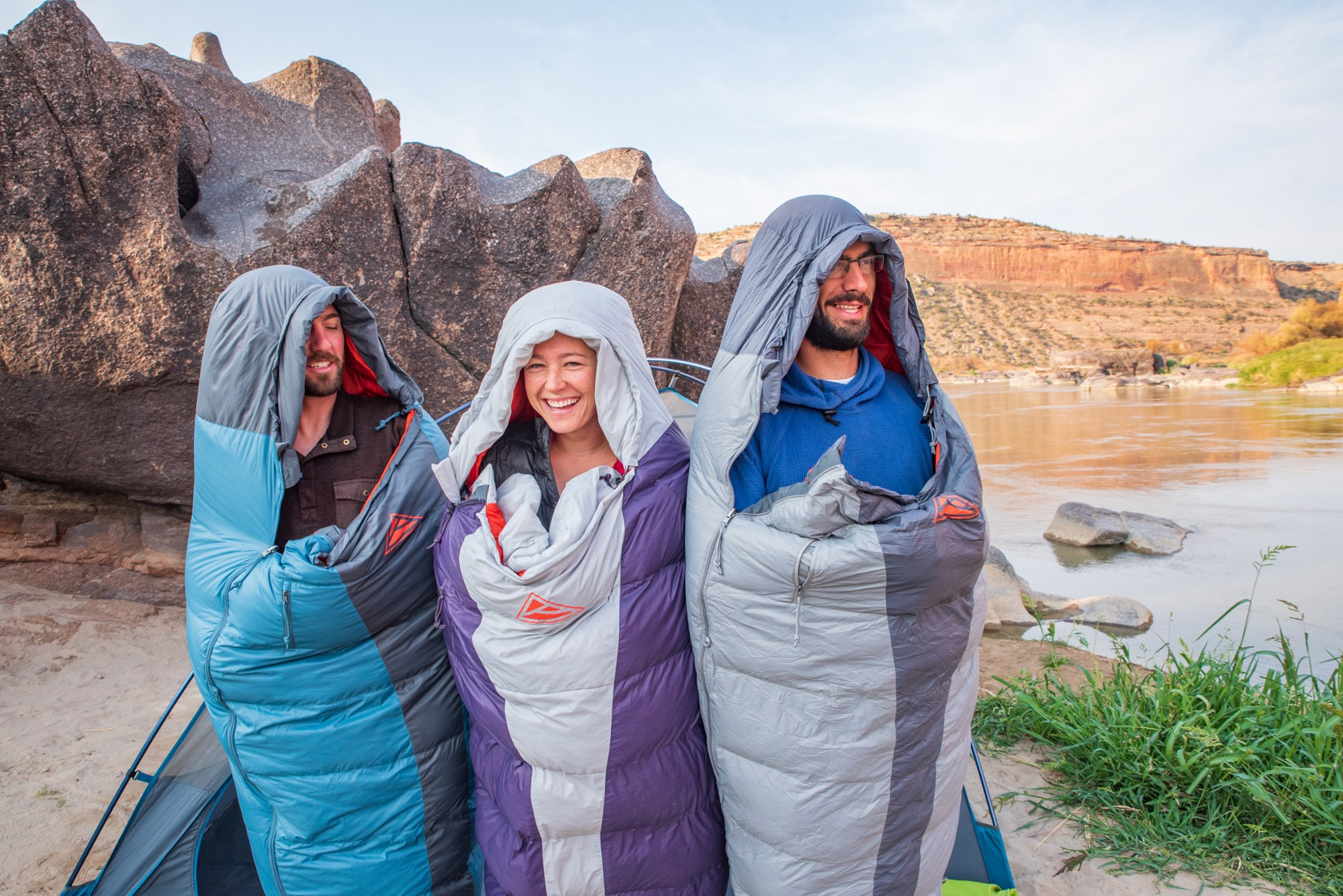 3 people wrapped up in sleeping bags, standing in a canyon outside