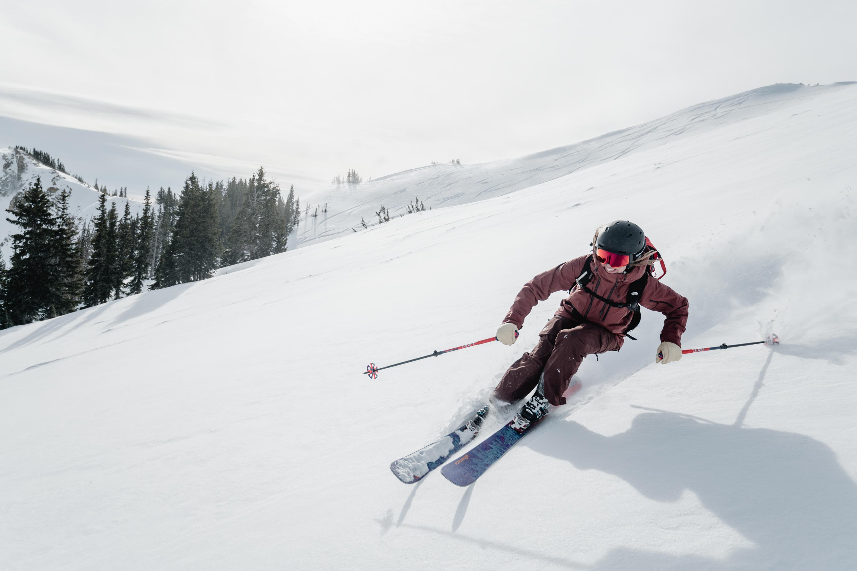 female skier in maroon jacket downhill skiing