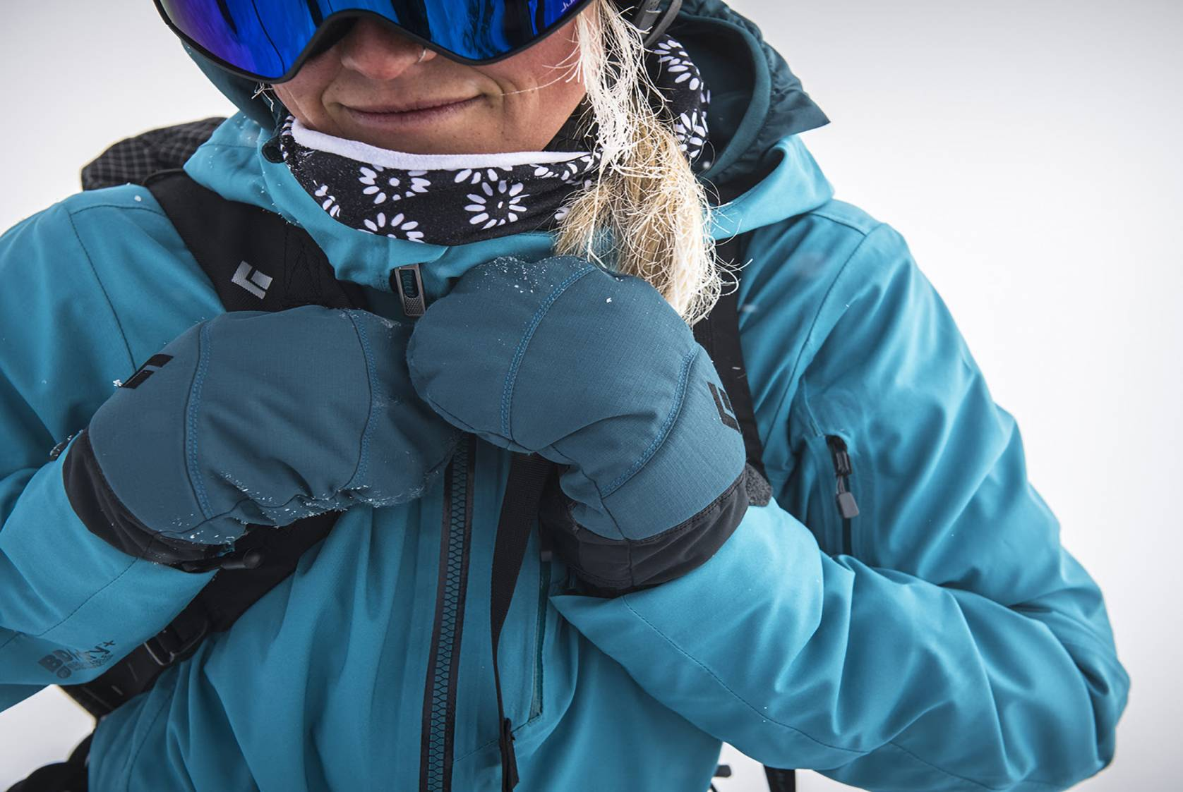 Person Wearing Black Diamond blue softshell jacket and blue insulated mittens and goggles