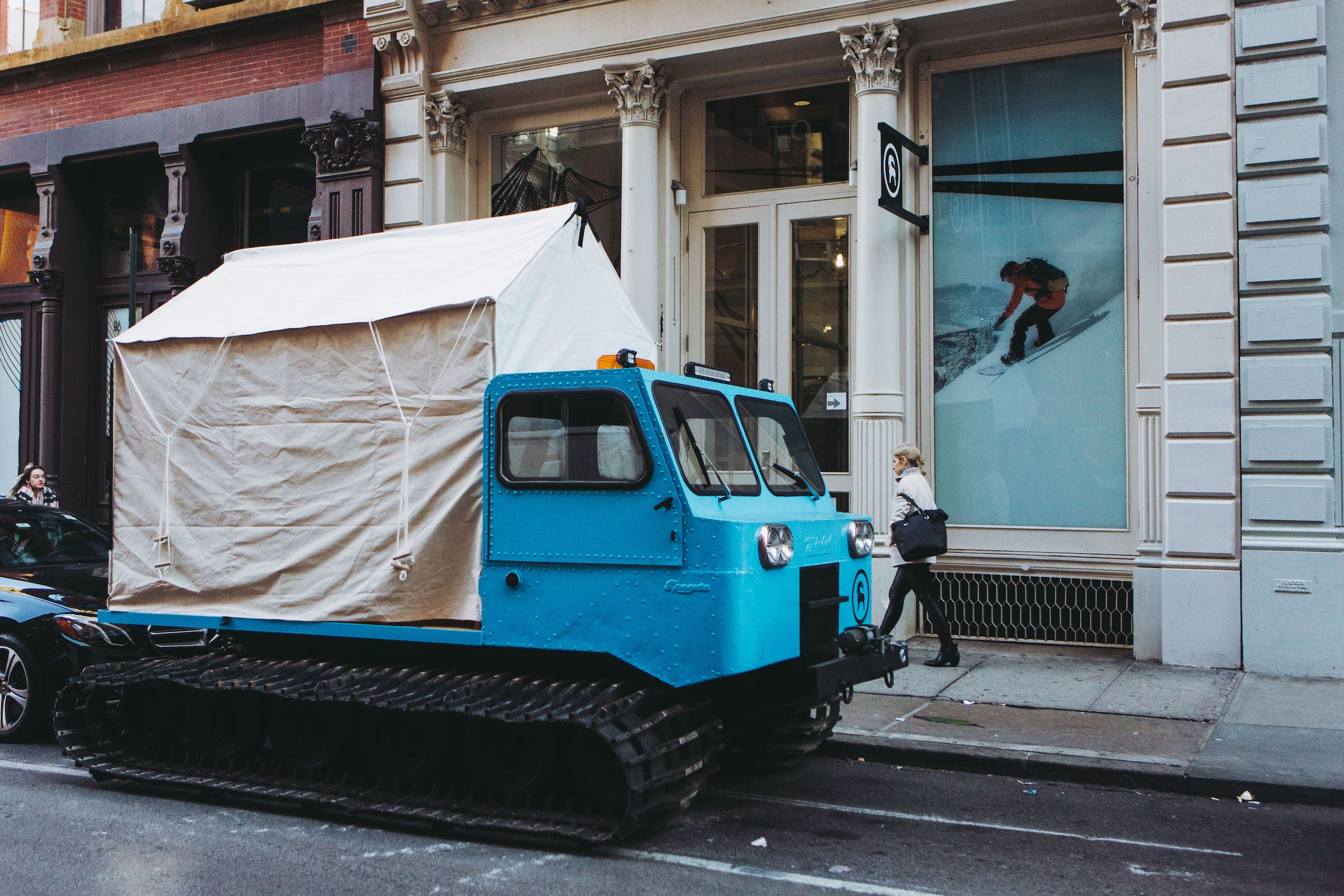 Backcountry storefront with blue snowcat parked outside on street