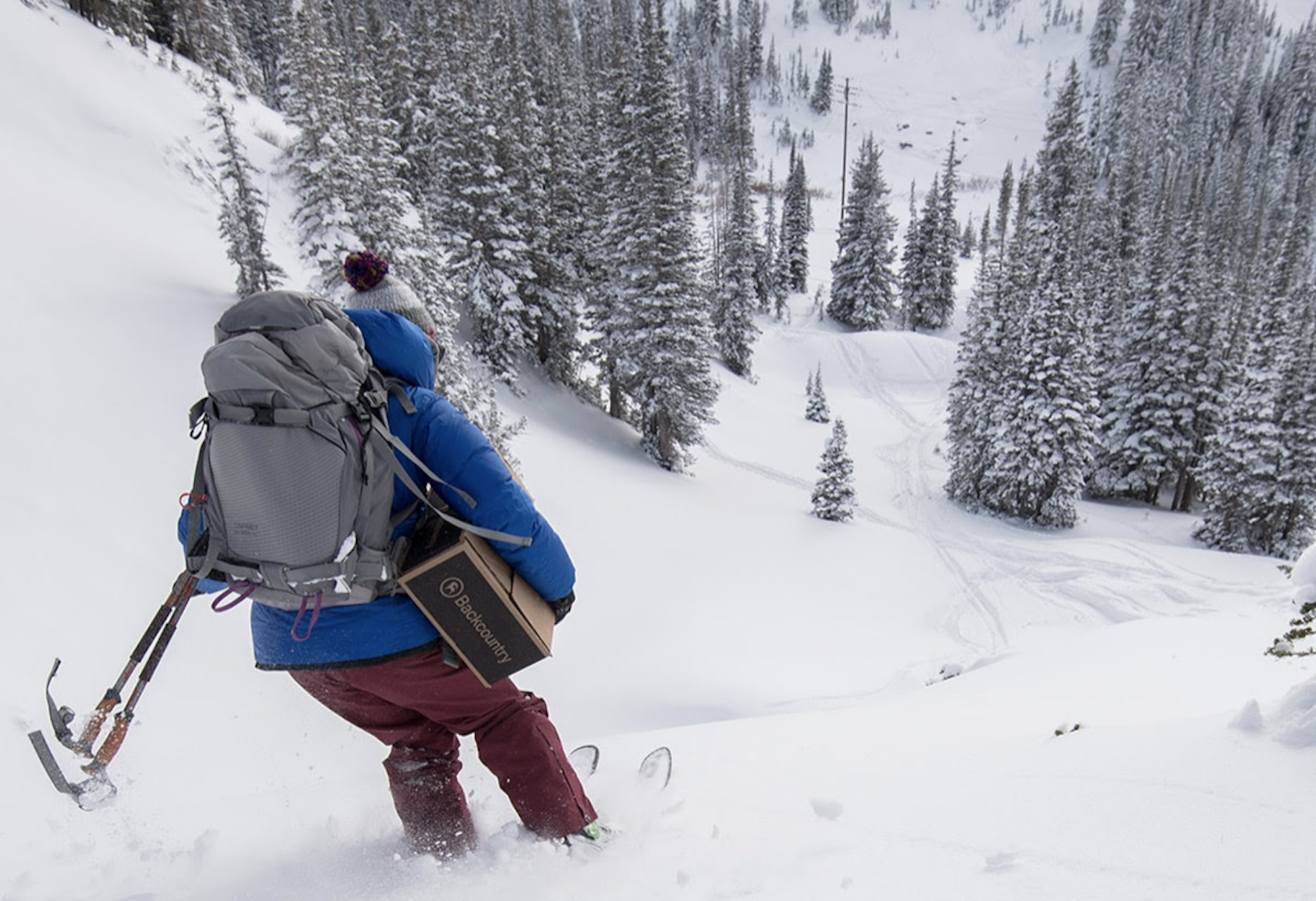 backcountry skier carrying a gift box under arm wearing ski pack and beanie